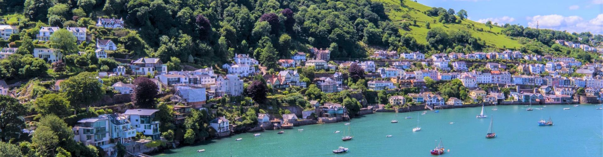Aerial view of coastal town on estuary with moored boats in South Devon small 3